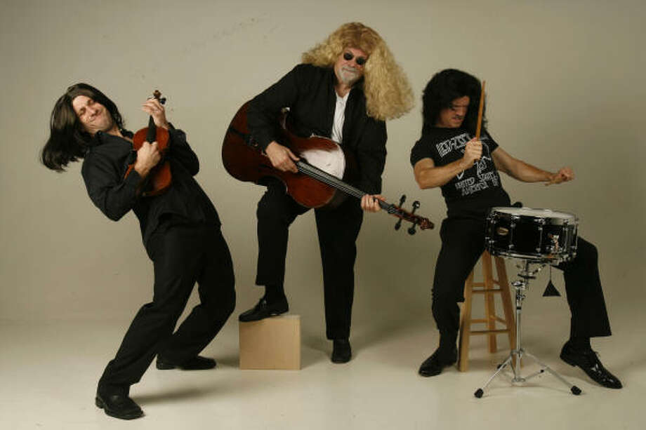 Houston Symphony musicians Matthew Strauss, from left, Charles Tabony and Christopher French  wearing wigs from Frankel's Costume Co., will be part of the Houston Symphony program The Music of Led Zeppelin: A Rock Symphony Friday at Jones Hall. Photo: Mayra Beltran, Chronicle