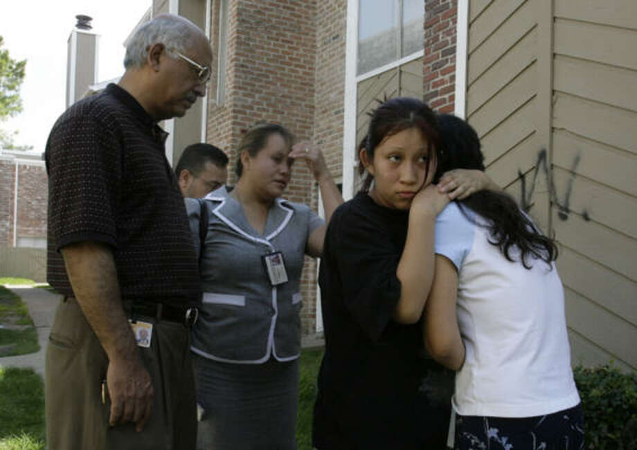 Ariadna Vazquez, 18, second from right, comforts her mother, Elvira Vazquez, as family members of David Vazquez, 10, mourned his death on Thursday, July 17. Photo: Julio Cortez, Chronicle