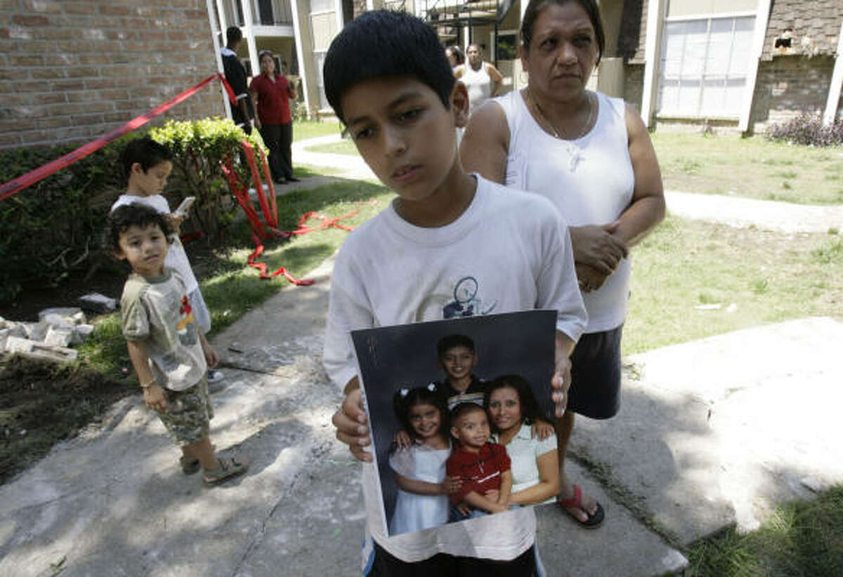 Alexis Robledo holds a family photo showing him on top with his sister Marisol Robledo, left, his brother Miguel Angel Robledo, center, and his mother Miguelina Robledo while standing halfway between his apartment and rubble at a collapsed staircase at the Westwood Fountains Apartments on Thursday.