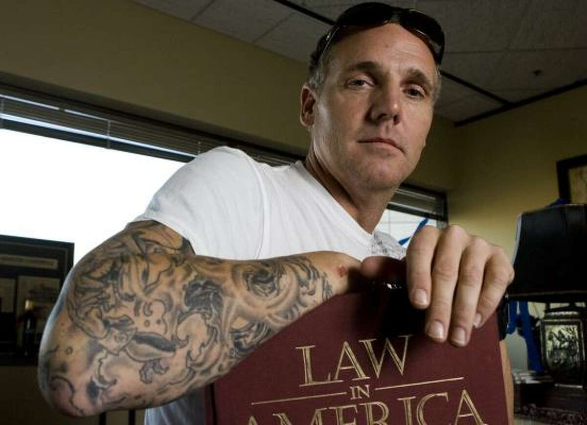 Newly elected State District Judge Kevin Fine shows his tattoos Friday in his downtown Houston office. Fine campaigned on his life experience of beating drug addiction, a story detailed in his tattoos.