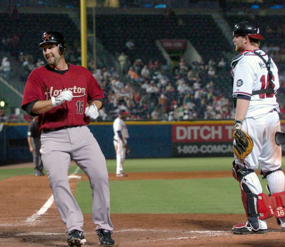 Jason Lane smiles as he runs past Braves catcher Brian McCann to score the go-ahead run on a single by pitcher Jason Jennings in the 14th inning.