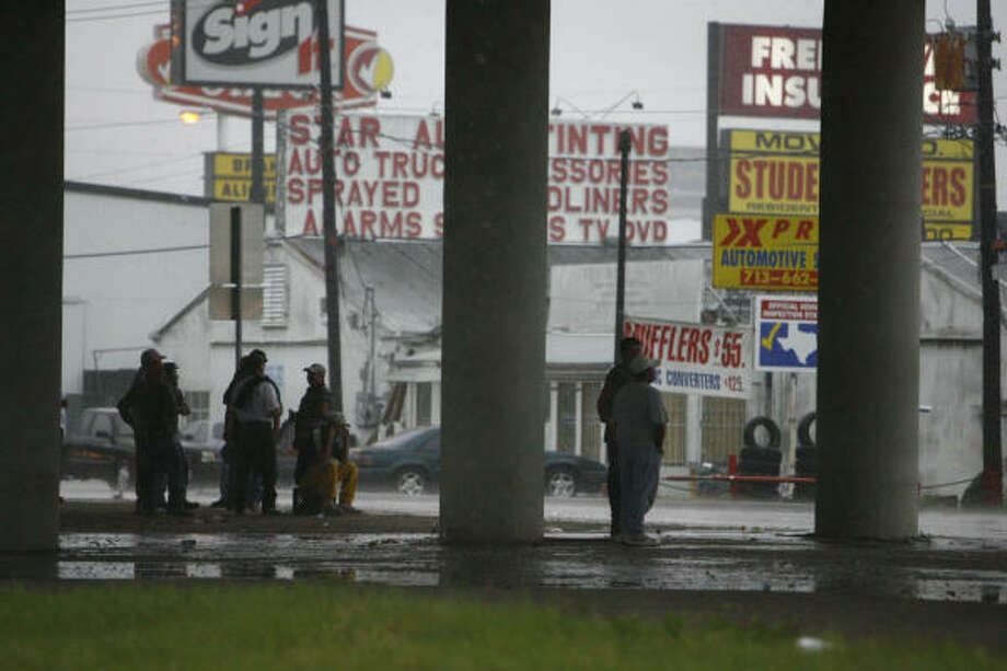 Day laborers take shelter beneath Highway 59 during heavy rain in southwest Houston on Thursday. Photo: Nick De La Torre, Chronicle