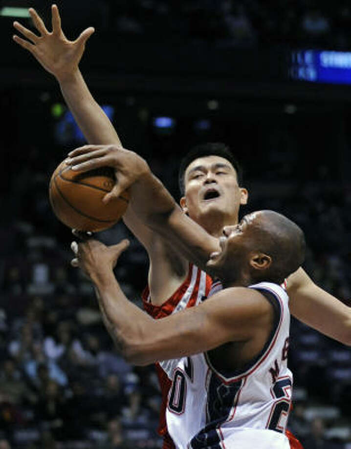 Yao Ming gets in the way of a drive by New Jersey's Jamaal Magloire. Photo: Bill Kostroun, AP