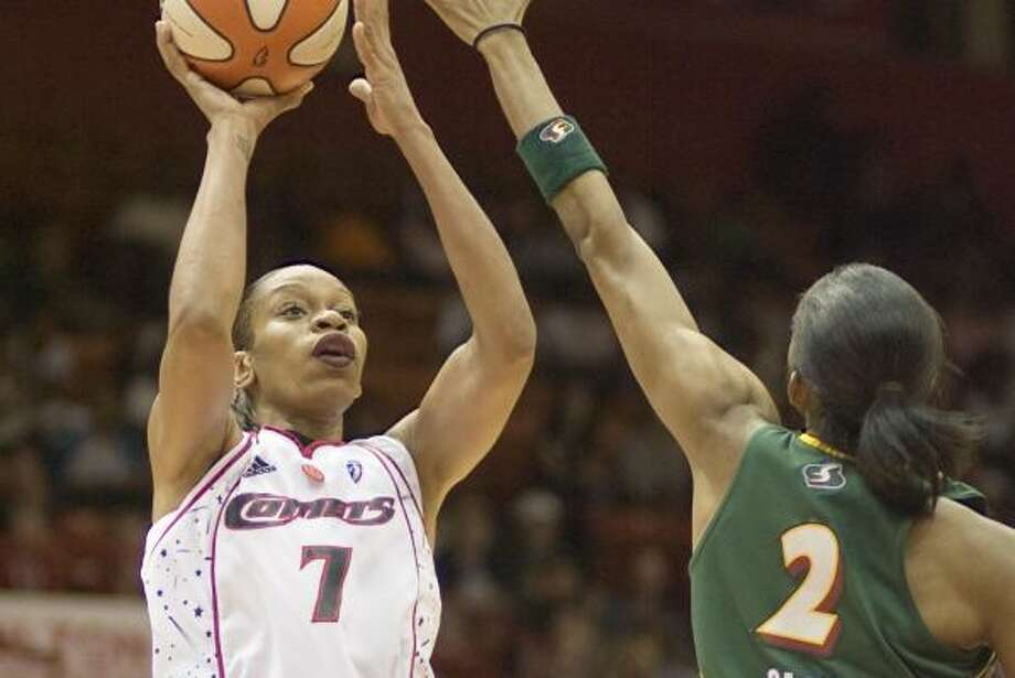 Comets forward Tina Thompson, left, shoots over Seattle's Swin Cash during the second half. Photo: Bob Levey, AP