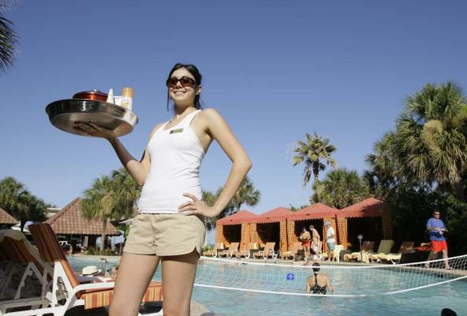 "Kalie Hatfield polishes sunglasses and sprays mist on sun bathers as a ""tanning butler"" at the San Luis Hotel's H2O Pool + Bar in Galveston. Houston-area hotels are diving into the national trend of high-end hotel pools combined with upscale bars. Photo: MELISSA PHILLIP, CHRONICLE"