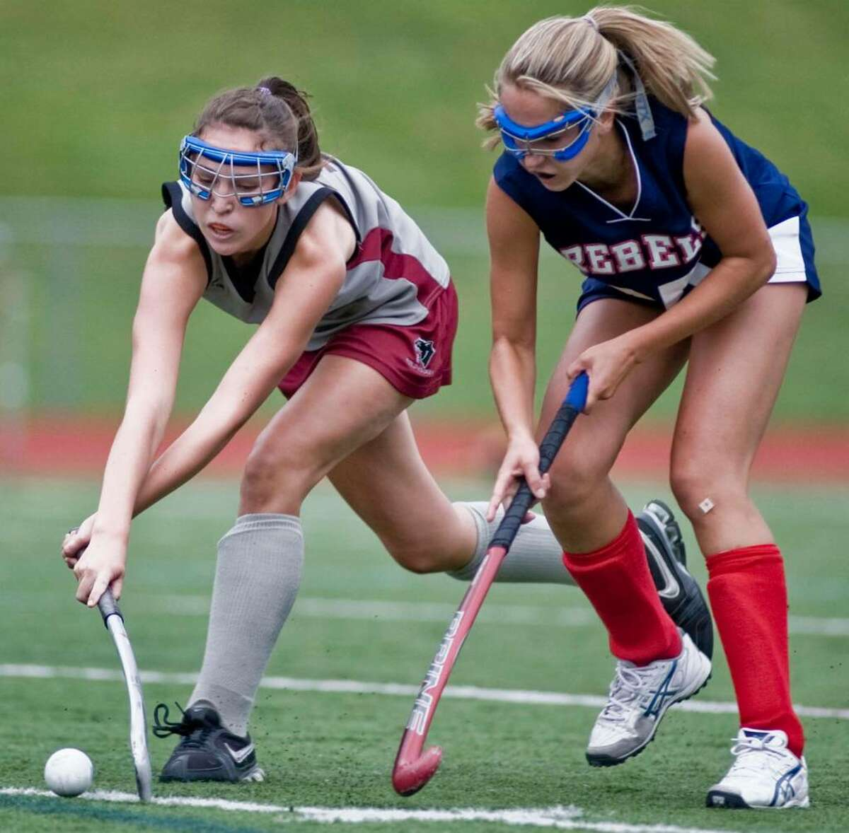 Pomperaug's Abby Dwyer and New Fairfield's Niki Van Houten battle for the ball during a field hockey game at Pomperaug. Tuesday, Sept. 29, 2009