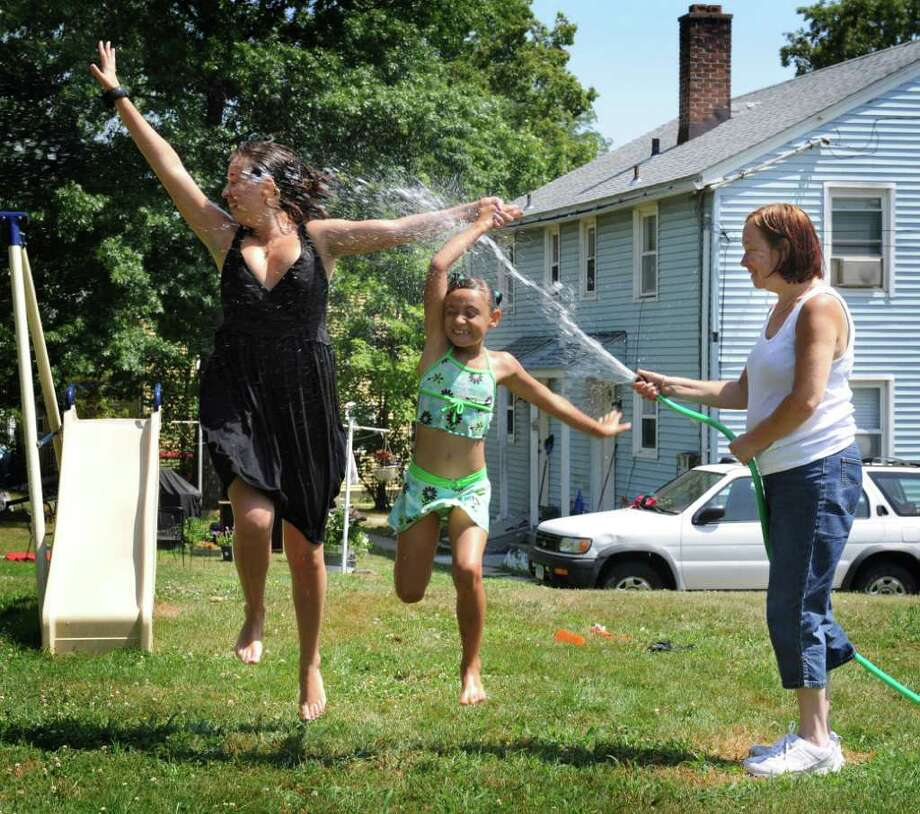 Mary Chmelko holds the hose for her daughter Melissa and grandaughter, Aaliyah, 7, to run through. The family was trying to keep cool at their home on Mill Ridge Road in Danbury Friday, July 22, 2011. Photo: Carol Kaliff