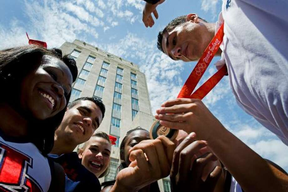 Steven Lopez shows off his bronze medal in taekwondo to a group of University of Houston cheerleaders during the Houston Olympic Heroes Day at City Hall on Tuesday in Houston. The event honored Houstonians who competed in the Olympics in Beijing. Photo: Smiley N. Pool, AP