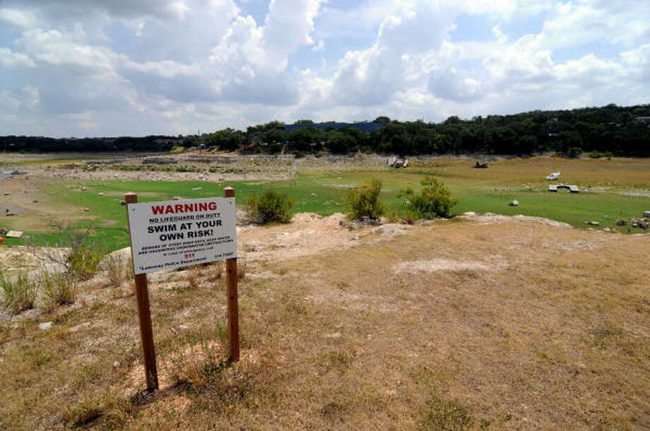Officials don't need to worry about swimmers in the Hurst Creek section of Lake Travis; it's gone dry because of the drought. The cove's Johnny Fins floating restaurant even had to relocate because of the lack of water. Photo: Patrick Meredith, For The Chronicle