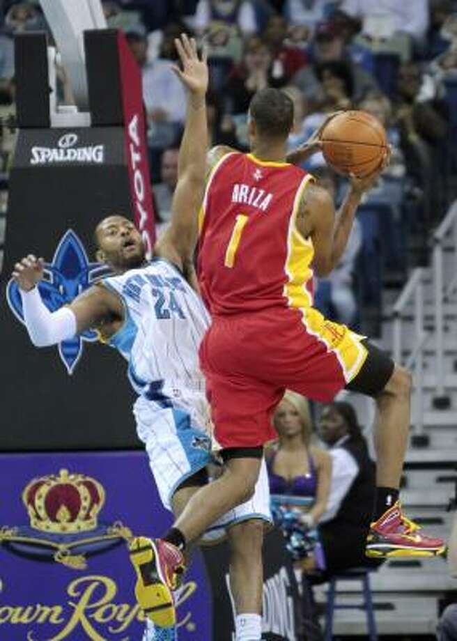 Rockets forward Trevor Ariza runs into Hornets guard Morris Peterson on a drive to the basket. Photo: Bill Haber, AP