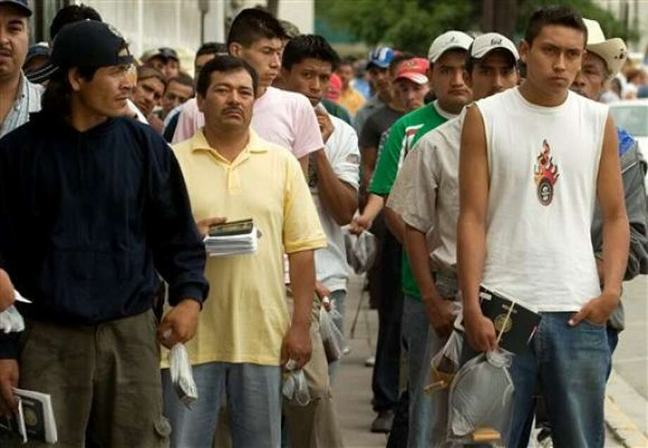 Mexicans line up outside the U.S. Consulate in Monterrey, Mexico, as they wait for interviews to obtain work visas. Photo: Guillermo Arias, AP