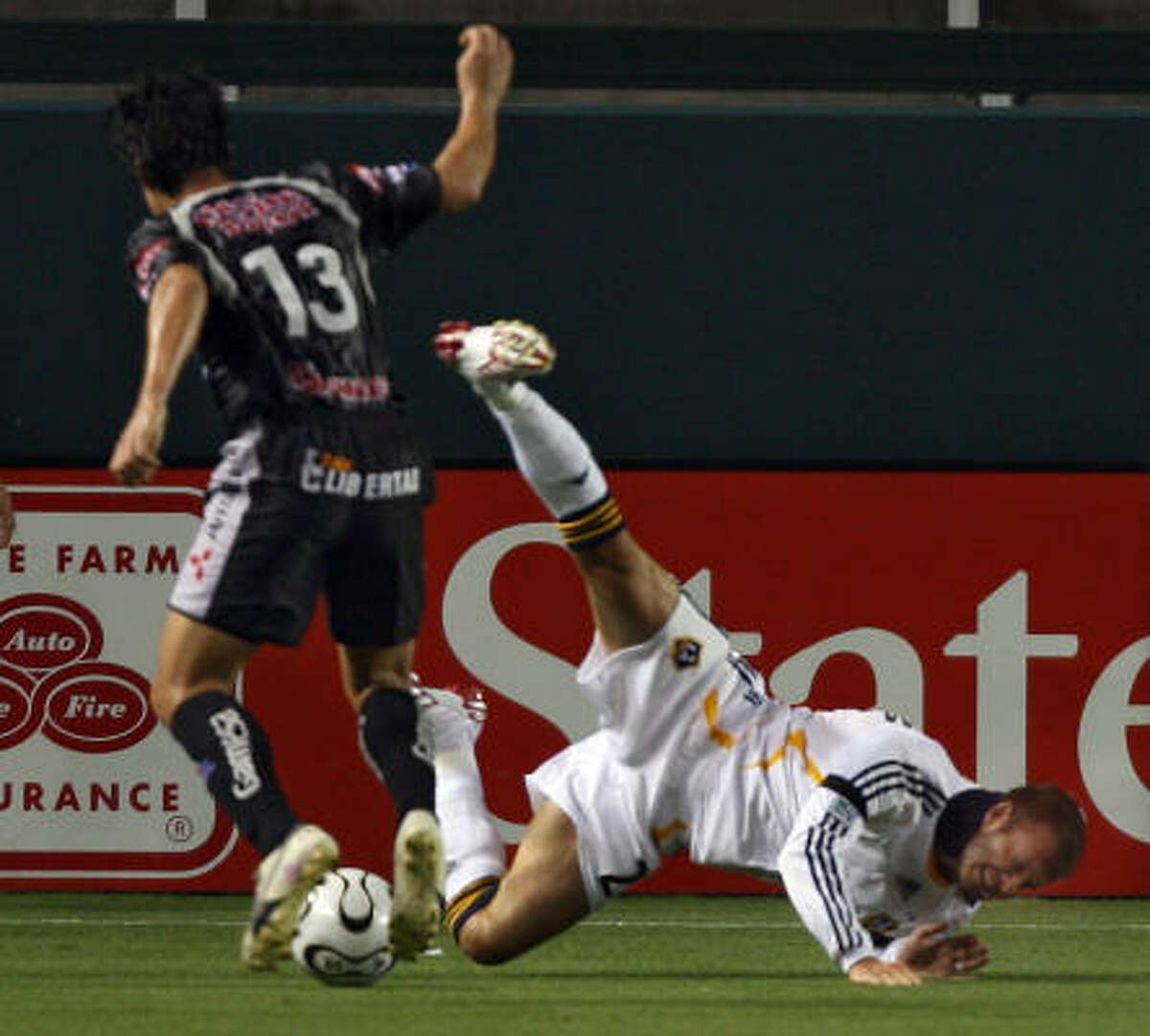 Los Angeles Galaxy midfielder David Beckham collides with Pachuca's Fernando Salazar (13) during the first half of Wednesday night's SuperLiga final at Carson, Calif. Beckham sprained his right knee on the play and had to leave the game in the 30th minute.