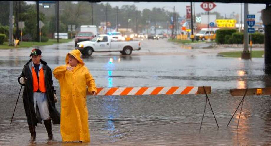 Madena Picard, left, and Judy Oldbury block off an underpass in Vidor after it was left flooded by Humberto's rains on Thursday. Photo: TAMMY McKINLEY, BEAUMONT ENTERPRISE