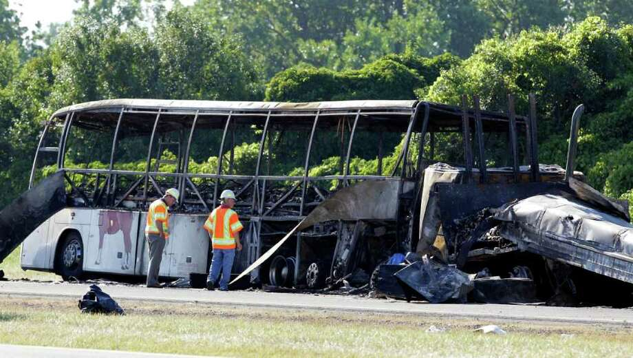 Workers evaluate the scene where a tractor-trailer crashed into a tour bus carrying about 50 people on the New York State Thruway in Waterloo, N.Y., Friday, July 22, 2011. The truck driver was killed and at least 20 people were sent to the hospital, state police said. (AP Photo/David Duprey) Photo: David Duprey