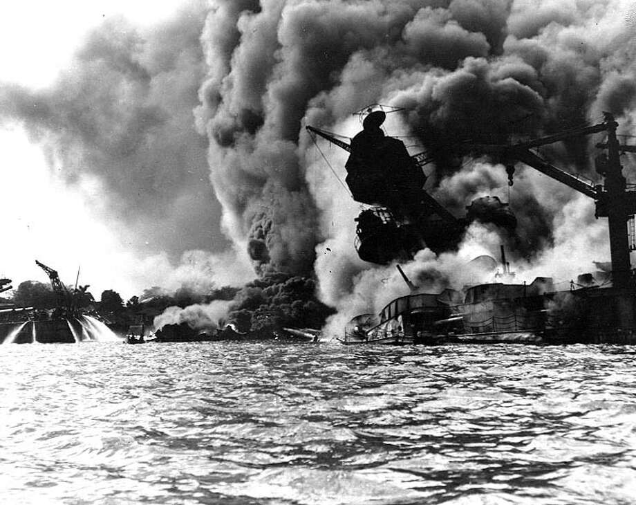 The USS Arizona burns after a Japanese bomb caused her forward magazines to explode on Dec. 7, 1941, at Pearl Harbor. At left, men on the stern of USS Tennessee are spraying fire hoses on the water to force burning oil away from their ship. Photo: U.S. Navy/National Archives Collection