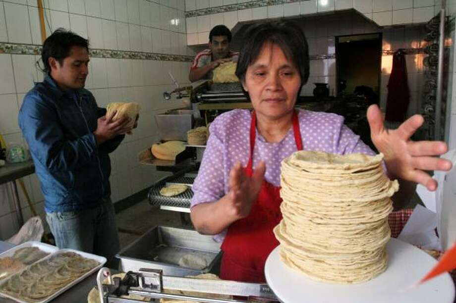 A woman works at a tortilla stand in Mexico City. An increase in the cost of tortillas has lowered the value of the peso. Photo: GUSTAVO GRAF, BLOOMBERG NEWS