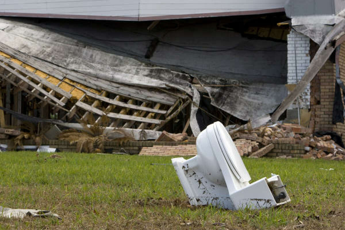 After being damaged from Hurricane Ike, a toilet is left in the yard of a Shoreacres home where two months later, many in the community still have yet to begin rebuilding Wednesday.