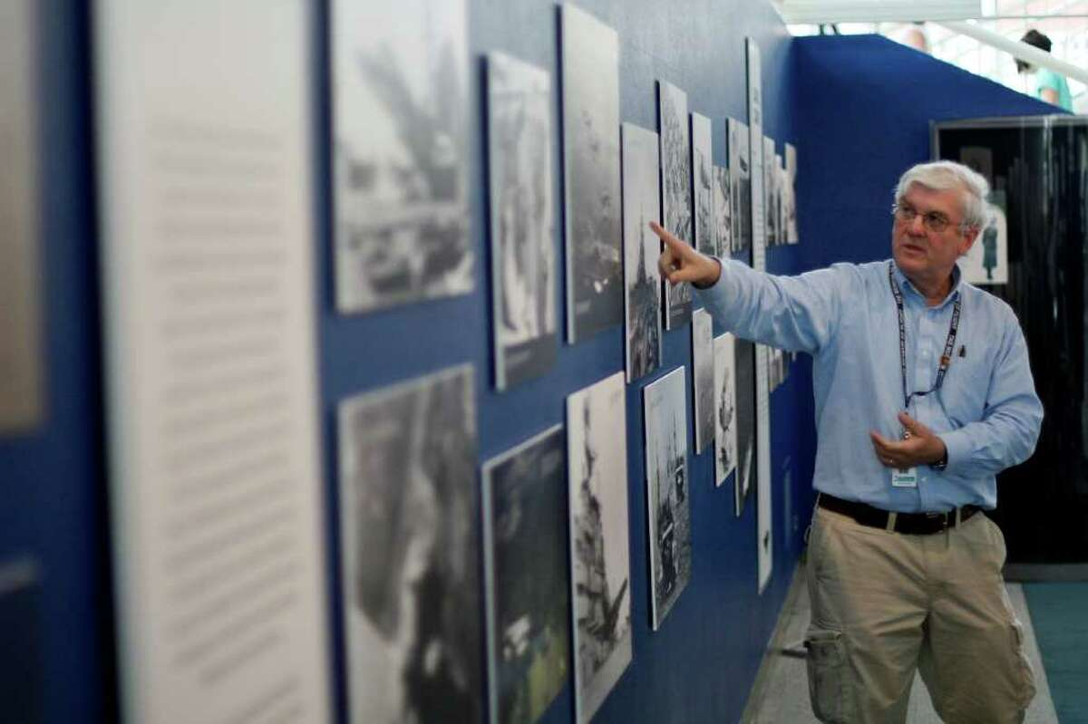 Volunteer Ted Young explains historical Navy photos at the Museum of Flight's new