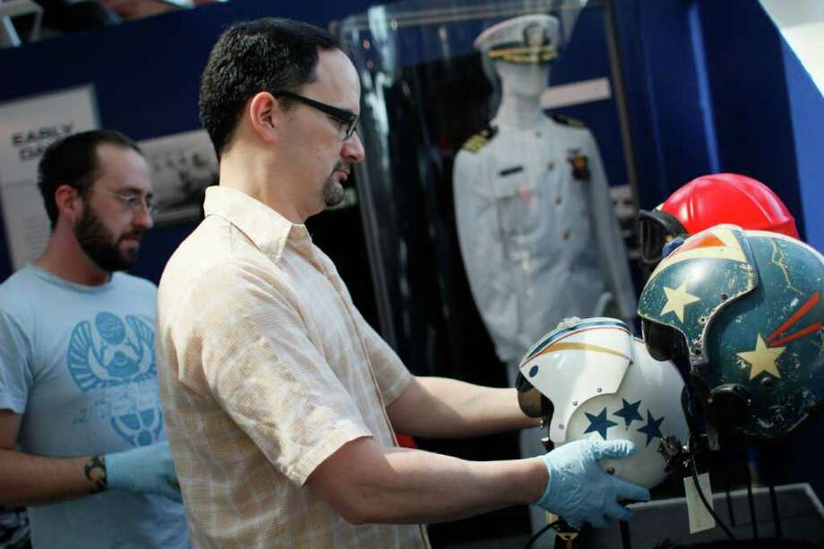 "Patrick Kam arranges Navy pilot helmets at the Museum of Flight's new ""Soaring at Sea: 100 Years of Naval Aviation"" exhibit in Seattle on Thursday, July 22, 2011. Photo: Joe Dyer/seattlepi.com"