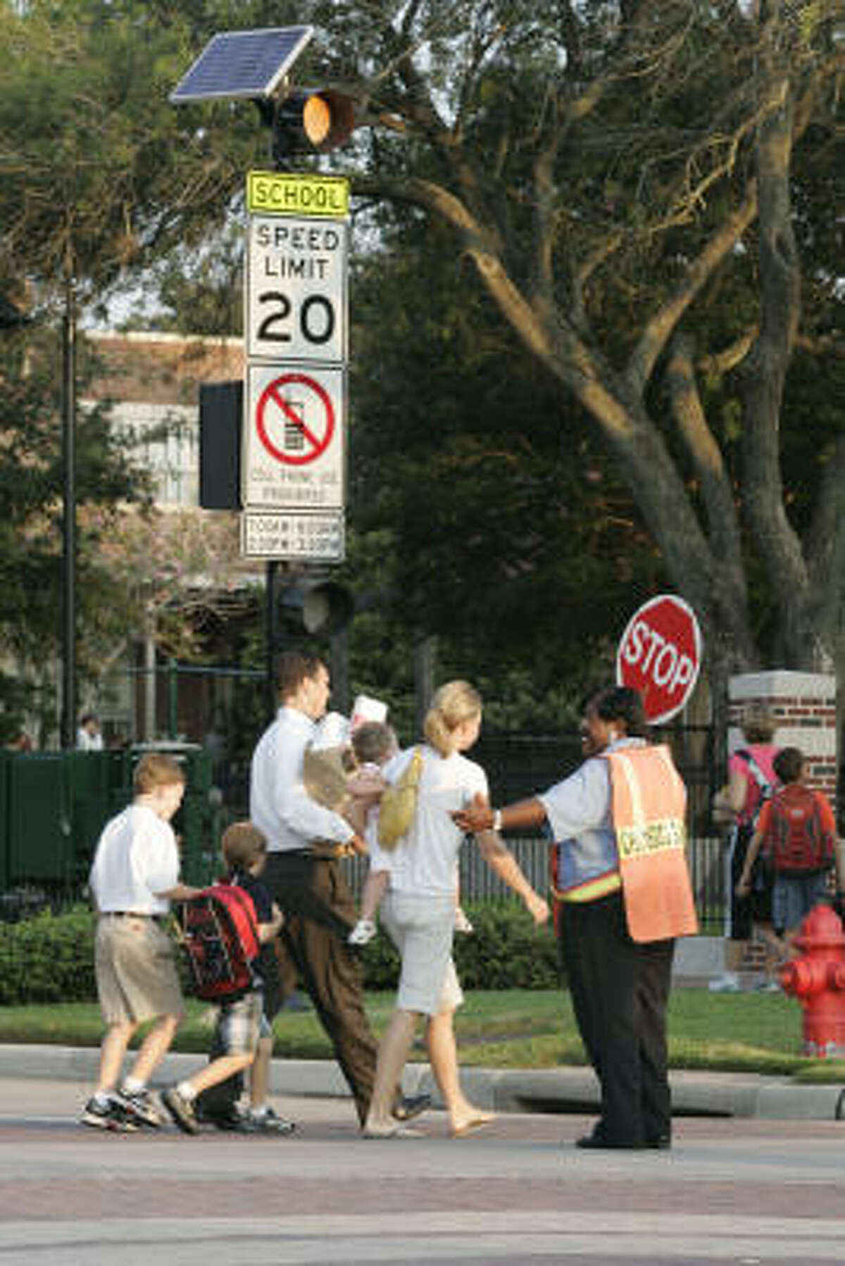 Crossing guard Pat Evans stops traffic this morning as parents and students head for West University Elementary School.