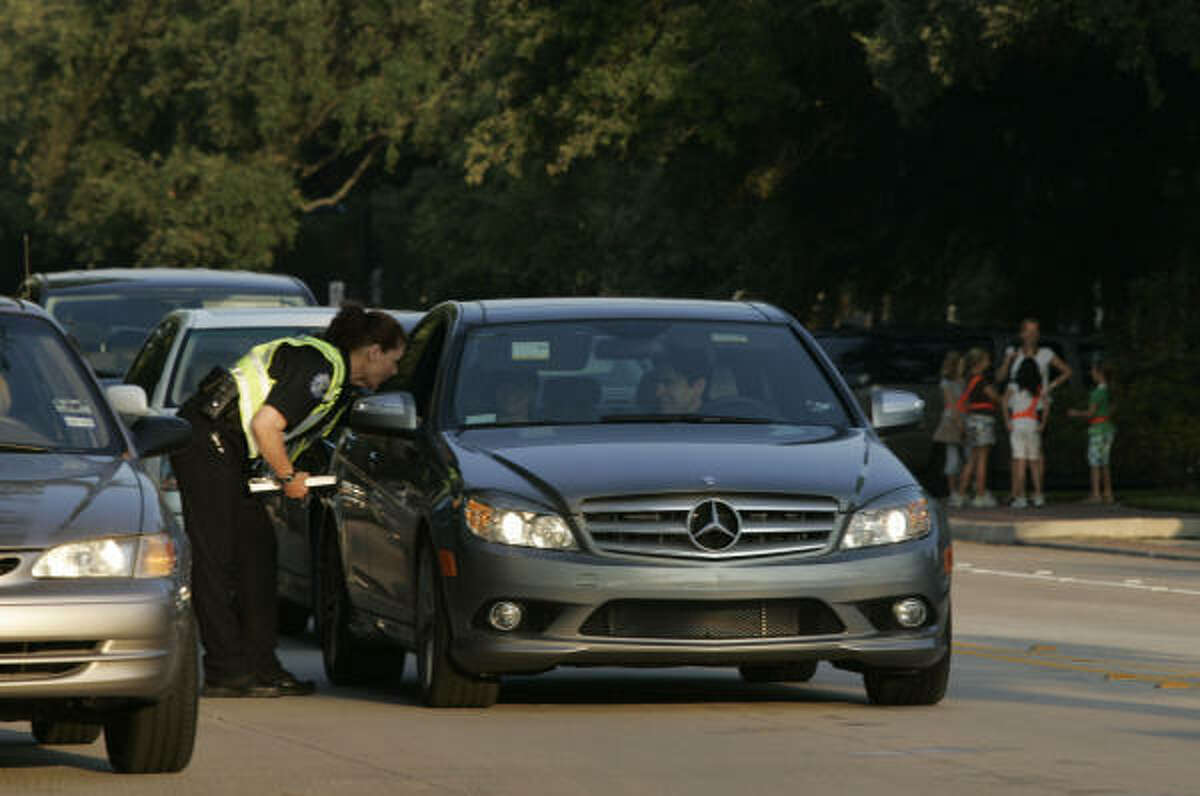 West University police Officer Merle Stewart gives a warning to a driver who was using his Blackberry as he drove by West University Elementary School on the first day of classes. The city has banned the use of cell phones and other electronic devices while driving in the school zone in the morning and afternoon.