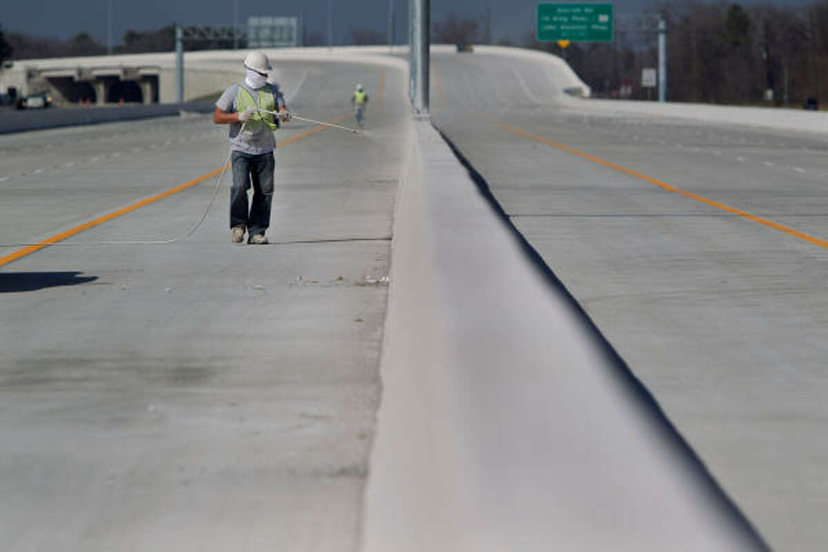 Victor Puzanenko puts finishing touches on the final stretch of the Sam Houston Tollway on Friday.