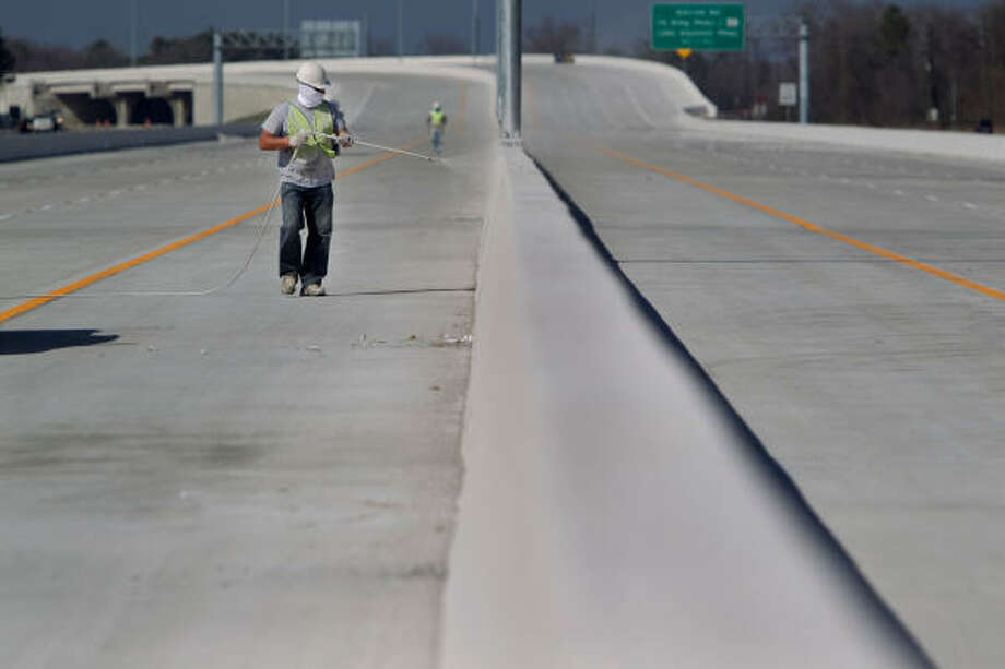 Victor Puzanenko puts finishing touches on the final stretch of the Sam Houston Tollway on Friday. Photo: Mayra Beltran, Chronicle