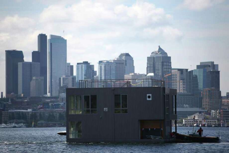 A floating home crosses Lake Union for Wards Cove, a floating home community in Seattle's Eastlake neighborhood, on Friday, July 22, 2011. The floating home slips at Wards Cove are billed as the last new floating home spots on Lake Union. The city is currently proposing a ban on new floating homes.  Photo: JOSHUA TRUJILLO / SEATTLEPI.COM