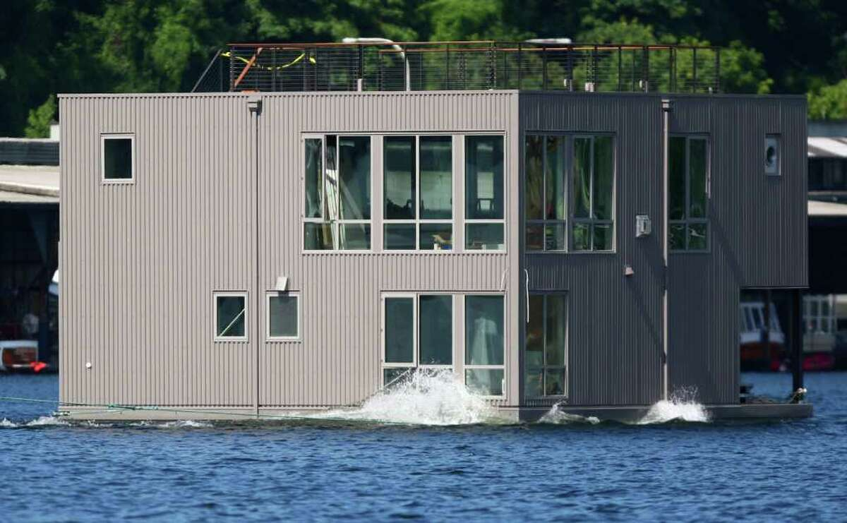 A floating home crosses Seattle's Lake Union, destined for Wards Cove, a new floating home community in Seattle's Eastlake neighborhood on Friday, July 22, 2011. The floating home slips at Wards Cove are billed as the last new floating home spots available on Lake Union.