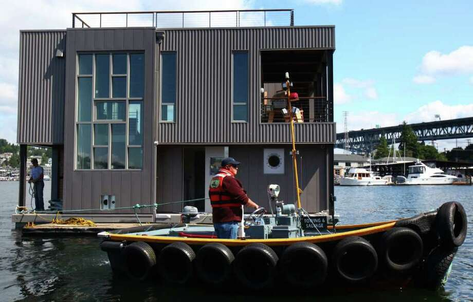A crew from Fremont Tugboat maneuvers a floating home that weighs more than 150 tons into Wards Cove on July 22, 2011 in Seattle's Eastlake neighborhood. The slips at Wards Cove are billed as the last new floating home spots on Lake Union. Photo: JOSHUA TRUJILLO / SEATTLEPI.COM