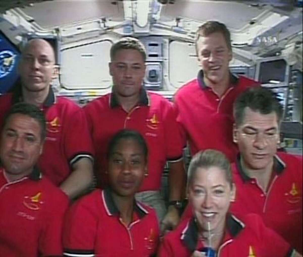 In this image from NASA TV, shuttle Discovery commander Pamela Melroy, lower right, answers a question during a news conference from space, Tuesday. Astronauts, front row from left, are George Zamka, pilot; Stephanie Wilson, mission specialist; Melroy and Paolo Nespoli. Back row, from left, are mission specialists Clayton Anderson, Douglas Whelock and Scott Parazynski.
