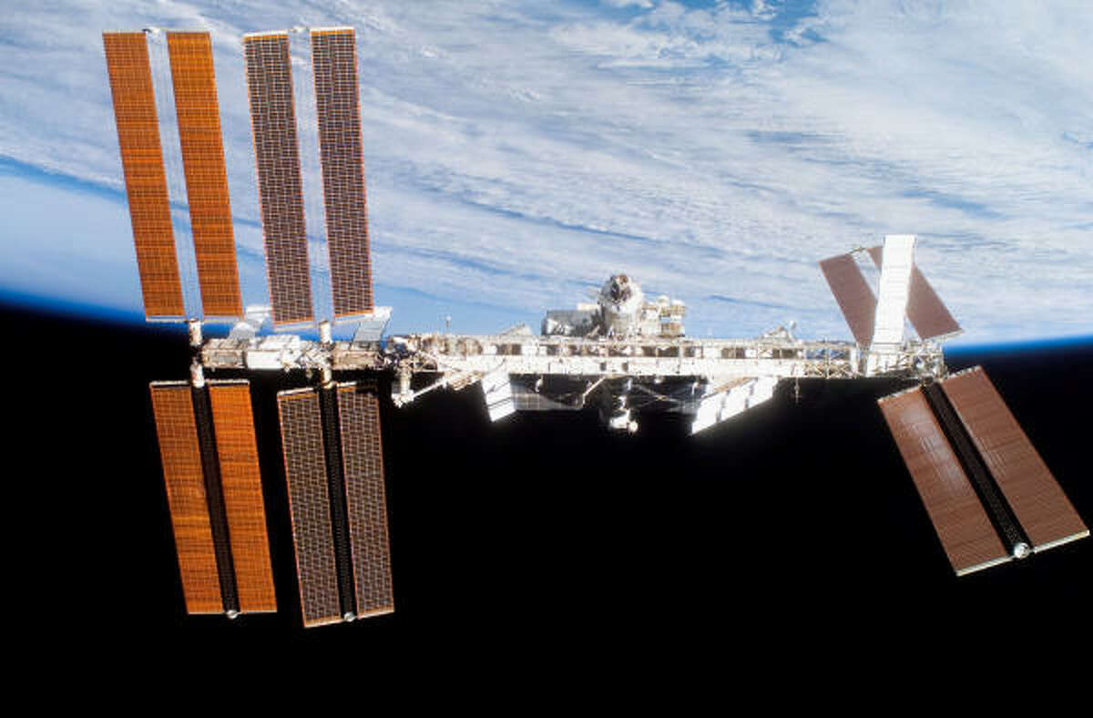 The international space station hangs on the horizon as seen after Discovery undocked Monday for the flight home.