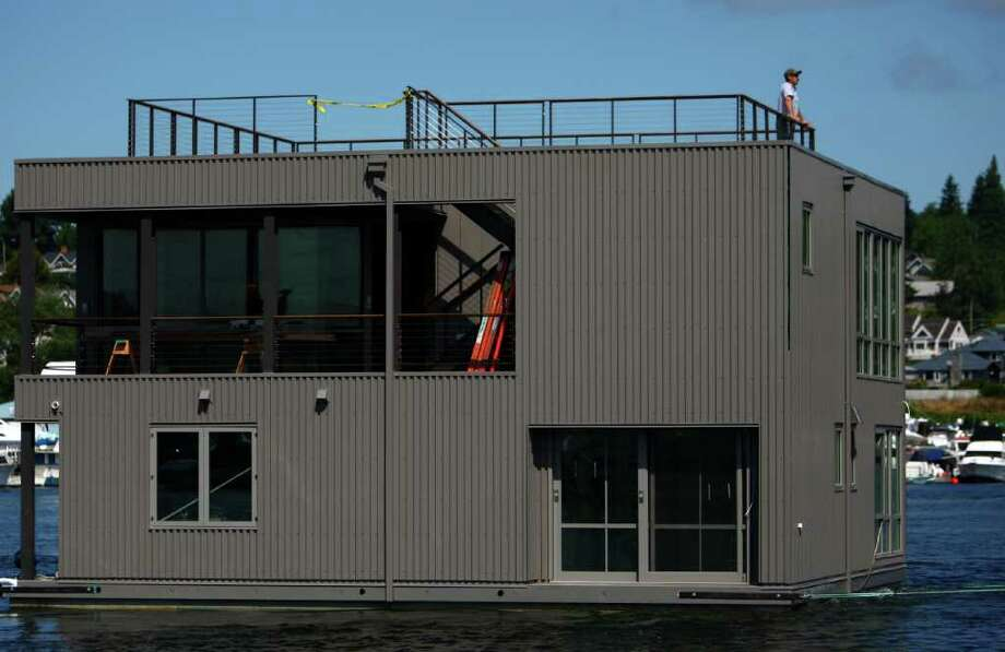 A floating home crosses Seattle's Lake Union, destined for Wards Cove, a new floating home community in Seattle's Eastlake neighborhood on Friday, July 22, 2011. The floating home slips at Wards Cove are billed as the last new floating home spots on Lake Union. The city wants to ban new floating homes.  Photo: JOSHUA TRUJILLO / SEATTLEPI.COM
