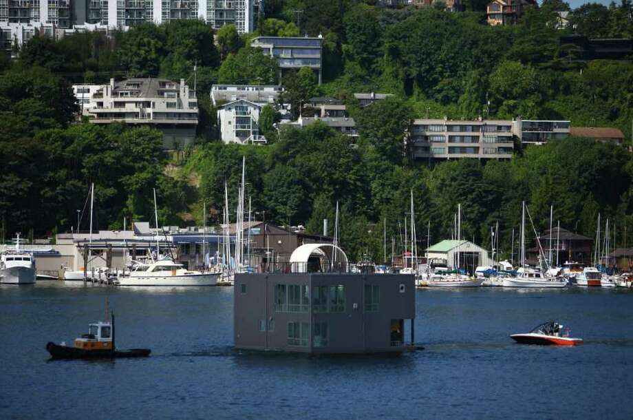 A floating home crosses Seattle's Lake Union, destined for Wards Cove, a new floating home community in Seattle's Eastlake neighborhood on Friday, July 22, 2011. The floating home slips at Wards Cove are billed as the last new floating home spots available on Lake Union. Photo: JOSHUA TRUJILLO / SEATTLEPI.COM