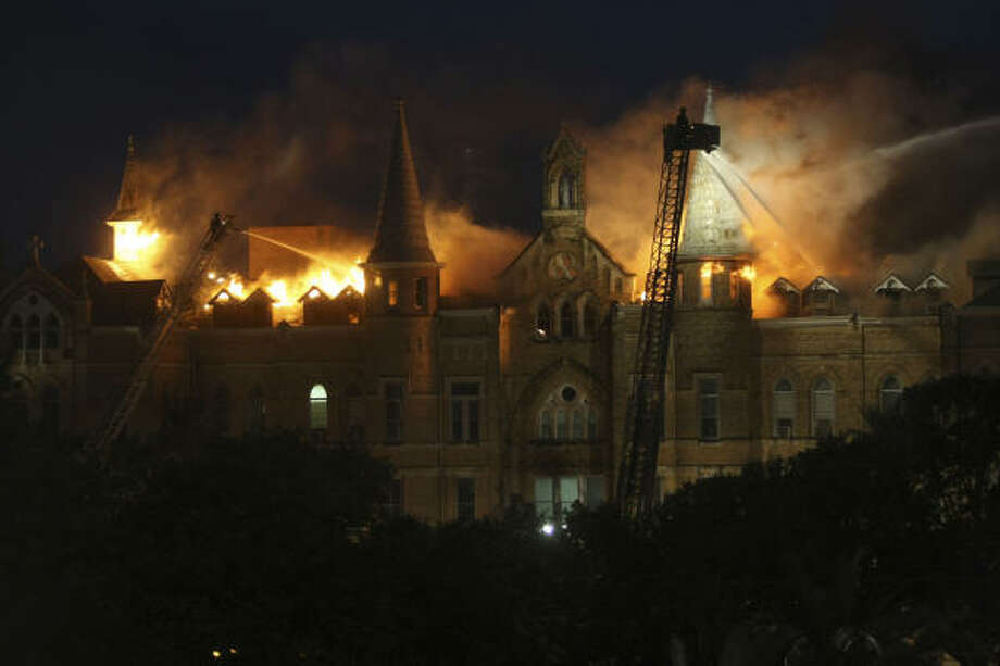 San Antonio firefighters spray water on the fire on the roof of the main buiding of  Our Lady of The lake University during a multiple alarm fire Tuesday. Photo: WILLIAM LUTHER, San Antonio Express-News