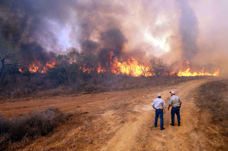 HELPLESS TO HELP  - Joe Herrera (left) and Len Polasek (right) of Texas Parks and Wildlife Department watch a line of wildfire burn across TPWD's Chaparral Wildlife Management Area on March 15. The fire burned about 95 percent of the 15,200-acre property in La Salle and Dimmit Counties south of San Antonio, causing no injuries and sparing most of the facilities but destroying a research building and several vehicles Photo: Chase Fountain, Texas Parks And