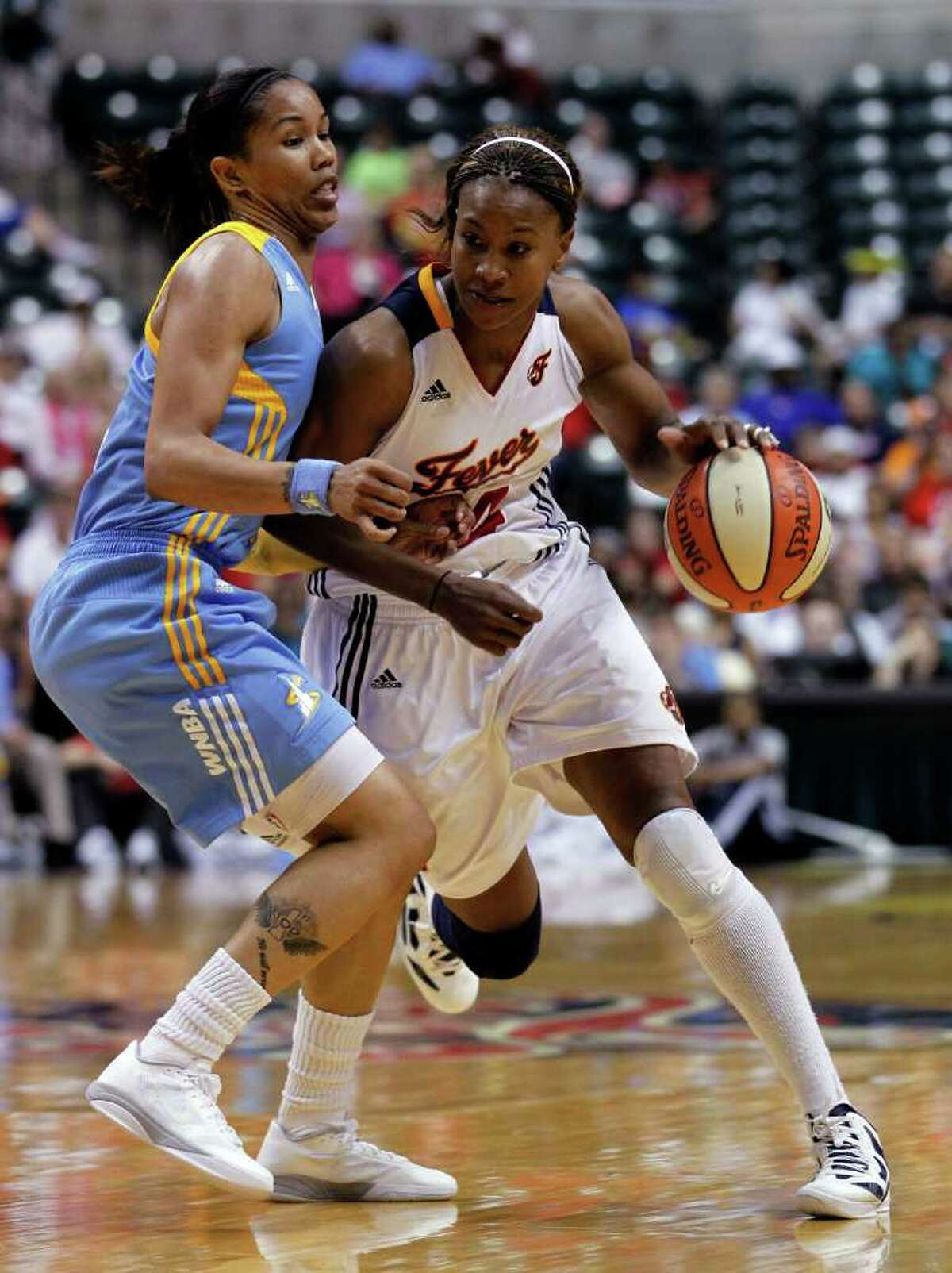 Indiana Fever forward Tamika Catchings, right, works the ball as Chicago Sky's Tamera Young defends during the second half of a WNBA basketball game in Indianapolis, Thursday, July 21, 2011. The Fever defeated the Sky 77-63. (AP Photo/Michael Conroy)