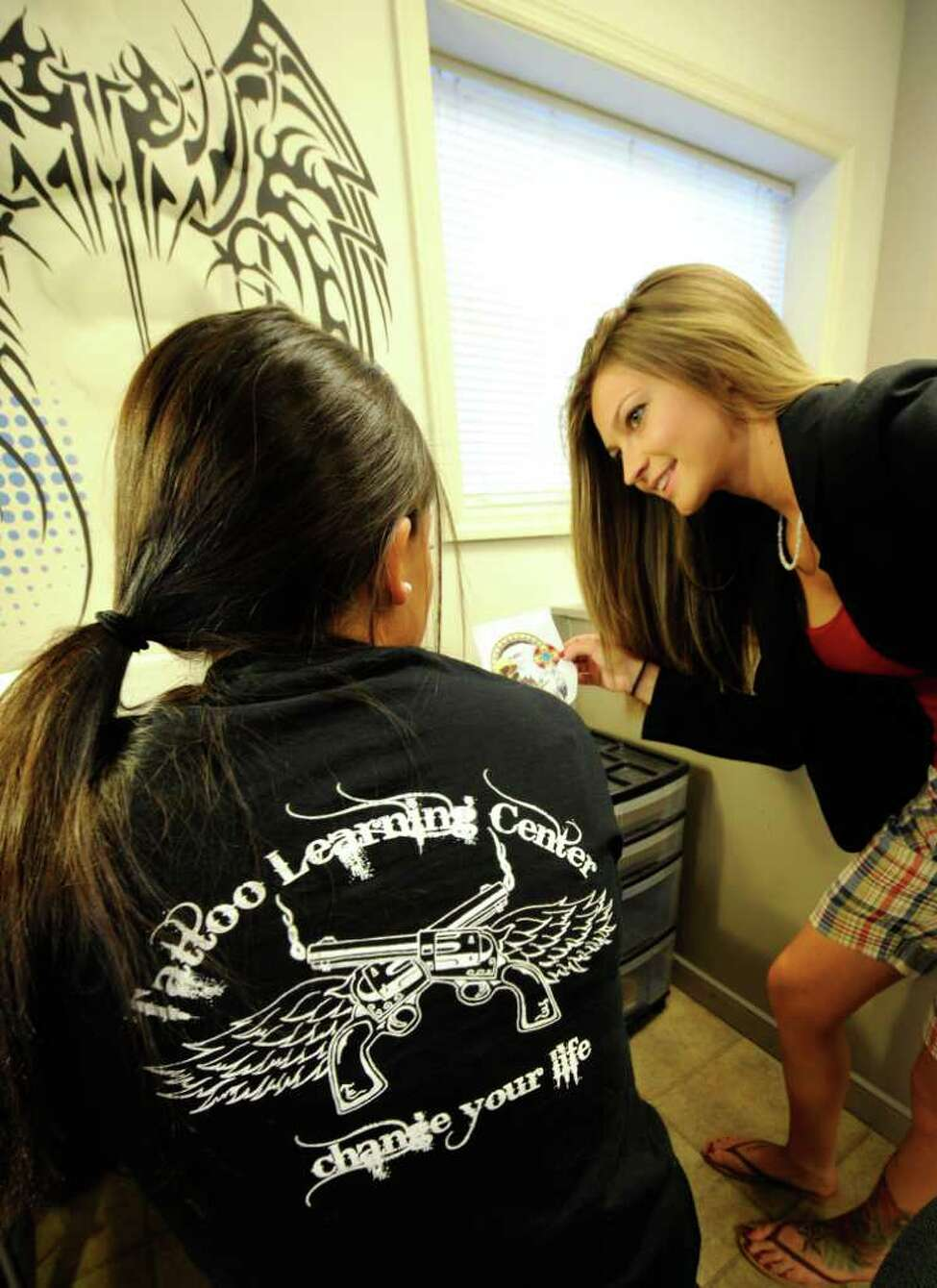 Lindsey Adams, teacher works with one of the students at the Tattoo Learning Center in Rotterdam, N.Y. July 15, 2011. (Skip Dickstein/ Times Union)