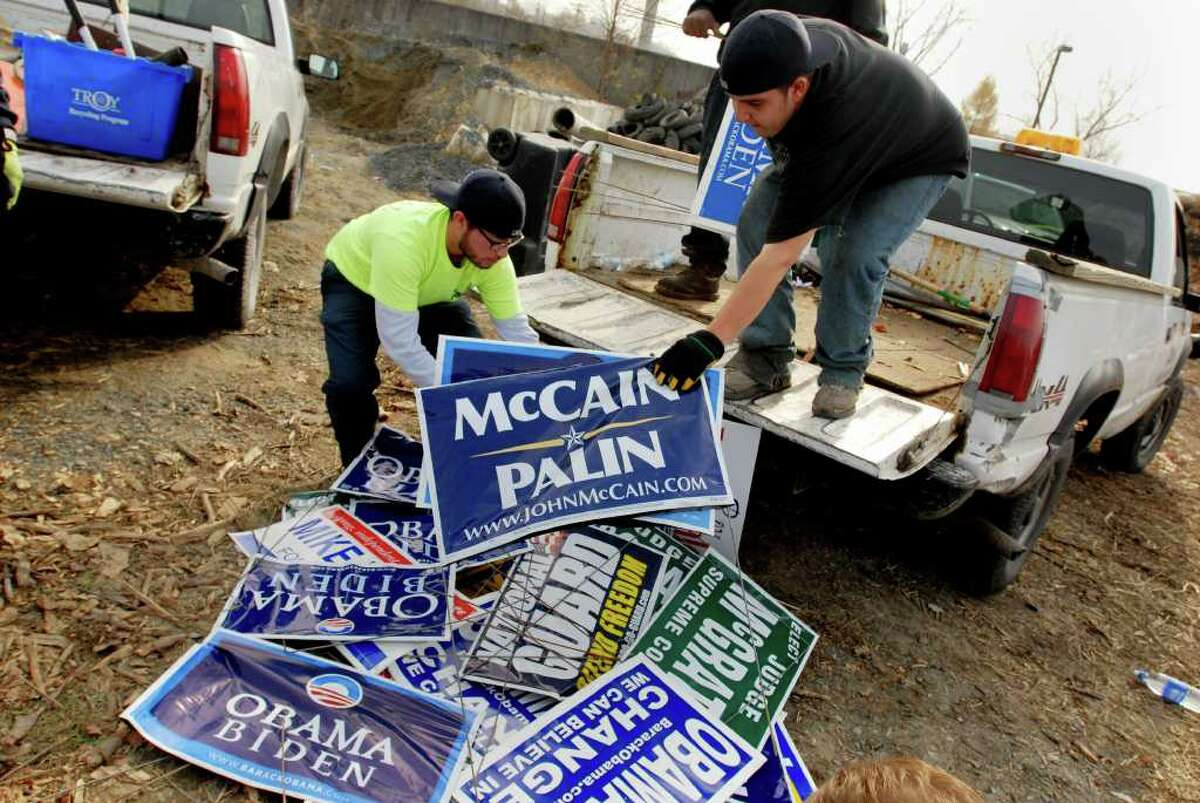 TIMES UNION / LUANNE M. FERRIS-- Members of Troy's Action Team, from the city's Dept. of Public Works, like L-R: Ty Treece, cq., and Chris Consuello, cq., carrying McCain/Palin campaign signs, went around the City of Troy collecting political signs and brought them to a central location in the south end, near the Rensselaer County Jail, for the campaigns to pickup, on Wednesday, Nov. 5, 2008. Under the direction of Public Works Commissioner Bob Mirch, cq., the men cleaned up the city just hours after the election, rounding up the once proud signs, now garbage.