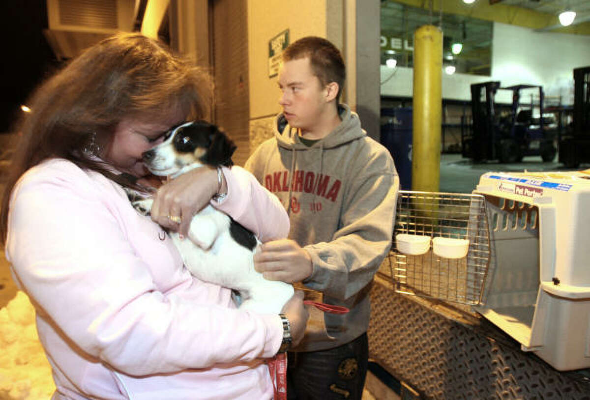 Vonda Lundstrom of Aurora, Colo., hugs Daisy at the Denver International Airport on Wednesday. Daisy was found by Tracie Crass in Knoxville, Tenn., who found the dog's owner through its rabies tag.