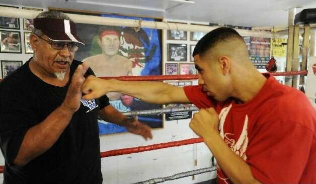 Boxing trainer Joe Lopez (left) works with undefeated junior welterweight James Cantu, his top pro prospect, on Thursday. Cantu faces Pharr's Juan Lucio tonight. BILLY CALZADA/gcalzada@express-news.net