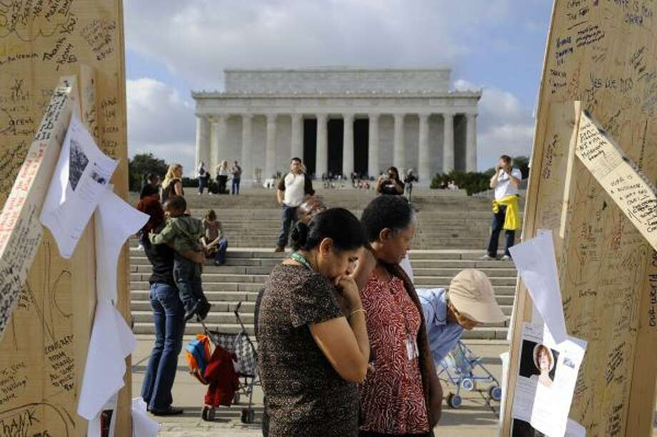 Anita Kapoor of Clarksburg, Md., center, and Donna Thomas are among visitors Friday writing messages to Barack Obama on a display in Washington, D.C., near the Lincoln Memorial. Photo: JACQUELYN MARTIN, ASSOCIATED PRESS