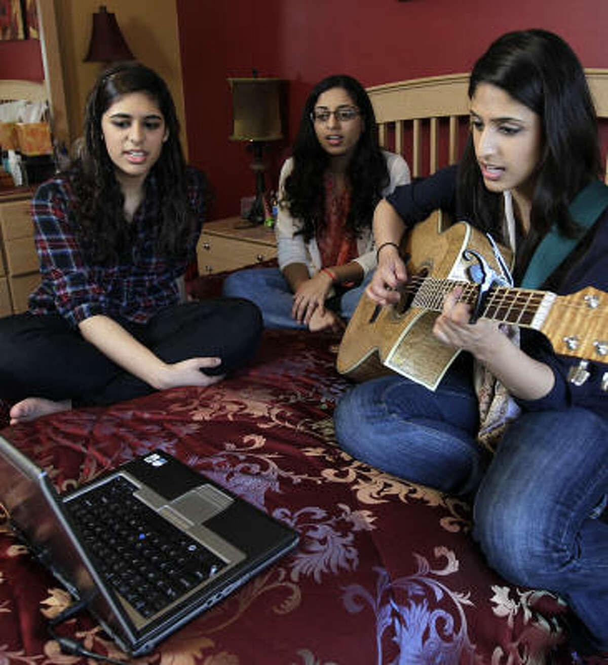 Asma Mirza plays guitar and sings with her sisters Ayesha, 16, left, and Hira, 18, at her Houston-area home. Born in Pakistan, Mirza has lived in the United States for 19 of her 20 years and is a naturalized American citizen.