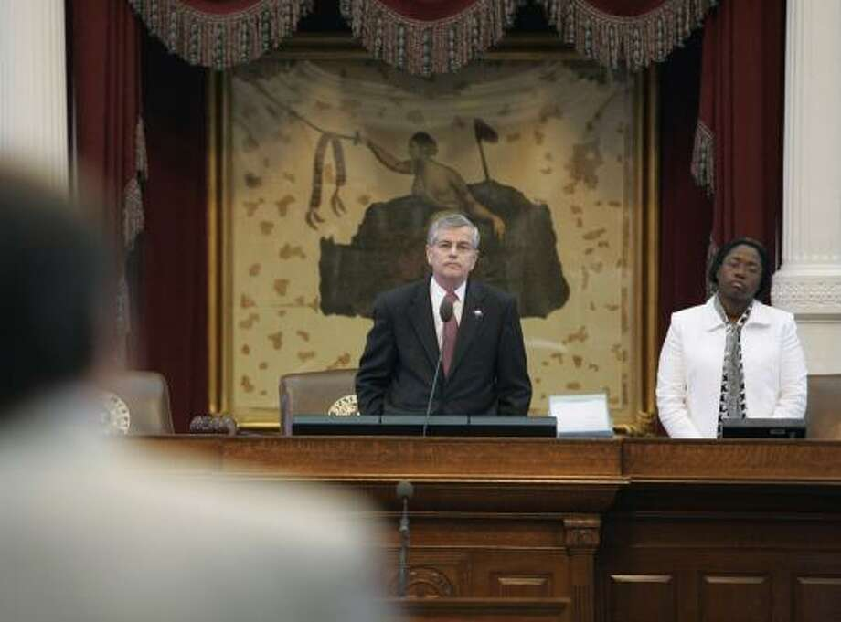 Rep. Jim Dunnam, D-Waco, foreground, raises a question during the evening session Friday in the Texas House in Austin. A parliamentary showdown flared between Speaker Tom Craddick, R-Midland, background on the left, and several lawmakers who want him ousted. Parliamentarian Denise Davis is on the right. Davis later resigned. Photo: Harry Cabluck, AP