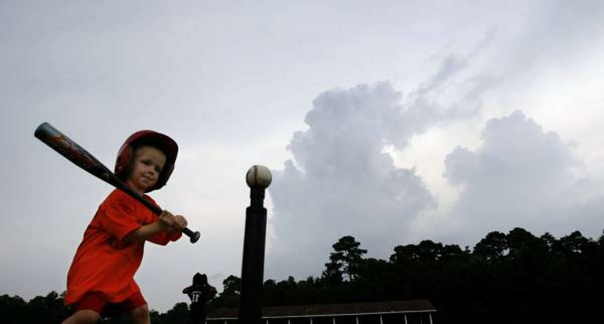 Landon Guyton, 4, gets set to take a swing off the tee as storm clouds loom in the distance. Officials at the South Montgomery County YMCA have wrestled with muddy fields and fire ants brought on by recent showers.