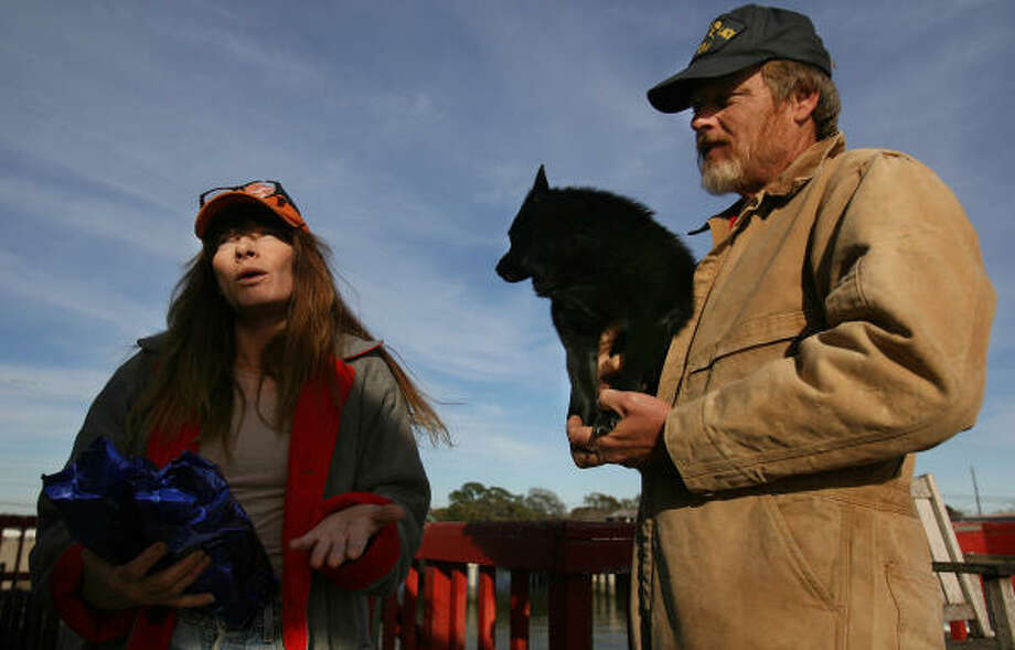 Terry Butcher talks about saltwater marks on the saved coffee bags from the sinking saiboat while her husband, Joe, holds Skipper. Photo: Mayra Beltran, Chronicle