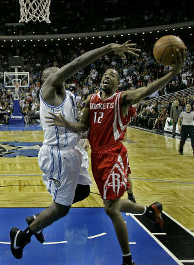 Rockets guard Rafer Alston (12) makes a shot over Magic center Adonal Foyle with 4.3 seconds left to help the Rockets escape Orlando with a 96-94 win Friday. Photo: John Raoux, AP