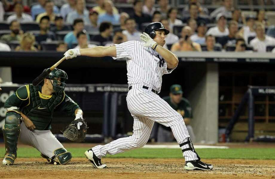 NEW YORK, NY - JULY 22:  Mark Teixeira #25 of the New York Yankees follows through on a third inning grand slam against the Oakland Athletics on July 22, 2011 at Yankee Stadium in the Bronx borough of New York City.  (Photo by Jim McIsaac/Getty Images) Photo: Jim McIsaac