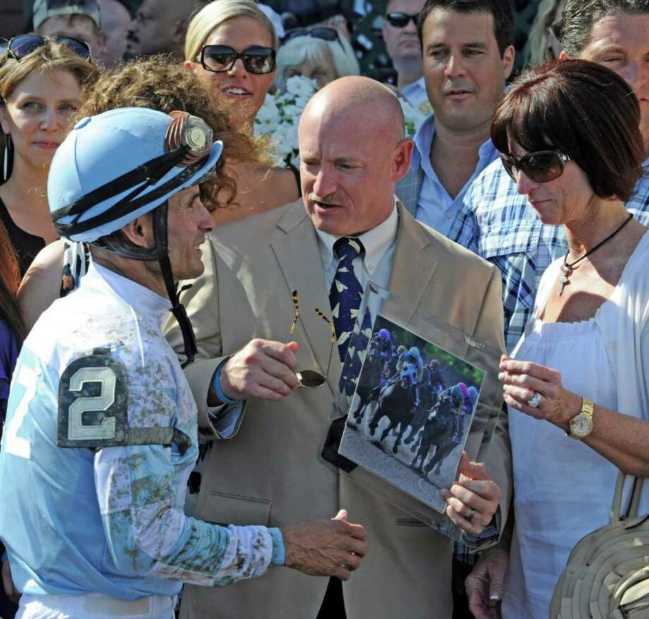 Astronaut Mark Kelly, center speaks with winning jockey Alex Solis, left and  Viane Lizza, right owner of the winner Pure Gossip in the winner's circle following the the 7th race on the card which was named for his wife Gabrielle Giffords at the Saratoga Race Course where he made the presentation of the winner's trophy  July 22, 2011.        (Skip Dickstein / Times Union) Photo: SKIP DICKSTEIN / 00013986A