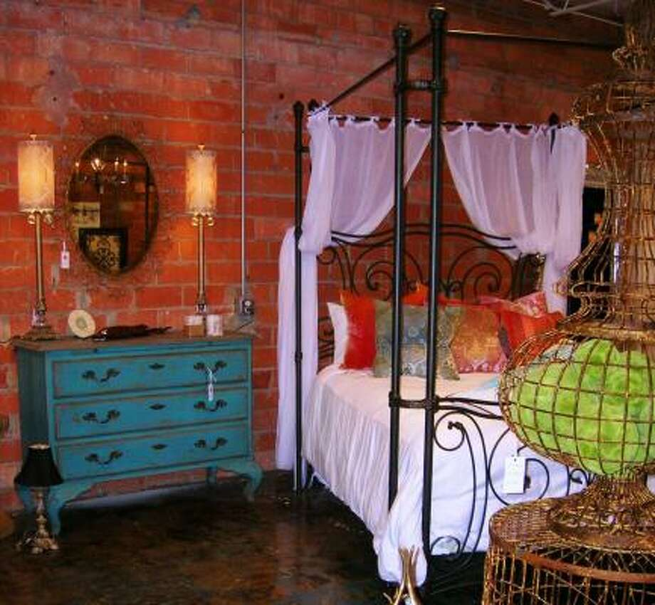 Decorative pillows adorn a huge canopy bed at the Laura U Collection boutique. Photo: LAURA U COLLECTION